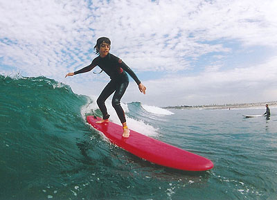 Boy surfing down the line at Eli Howard Surf Camp Overnight camps require a ...